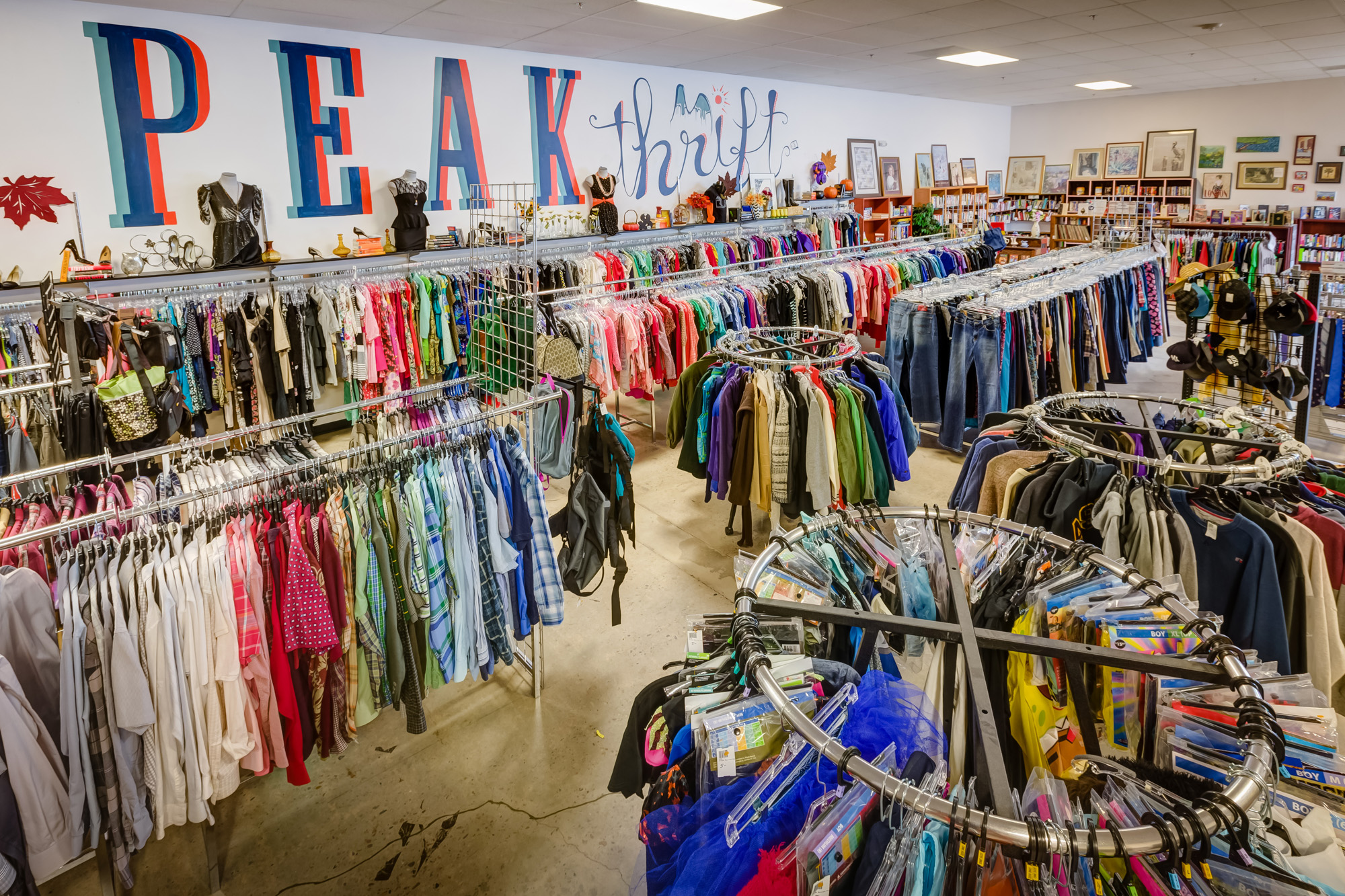 Interior of Peak Thrift with a high angle view of racks and shelves featuring colourful vintage clothing, accessories, and books.