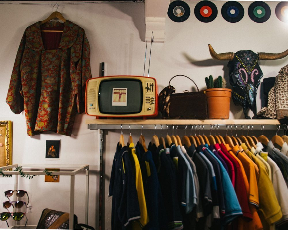 Thrift shop wall with a hanging rack of colourful vintage clothing with a shelf above full of quirky thrift finds such as a bull skull and retro television.
